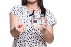 Tar den sydostliga asiatiska flickaåldern för den gulliga ungen 7 år preventivpiller eller vitamin l royaltyfria foton