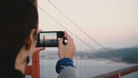 Tar den unga kvinnan för den tillbaka siktsnärbilden smartphonefotoet av att förbluffa solnedgången Golden gate bridge i San Fran arkivfilmer