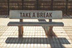 ` Tar en avbrotts`-text på konkret bänk på gatan arkivfoto