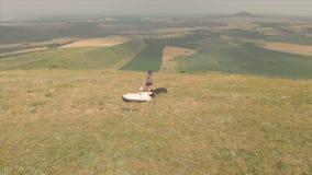 Tar går den yrkesmässiga paraglideren för den flyg- sikten efter landning, av utrustning och en hjälm och på en backe Paraglider arkivfilmer