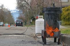 Tar Pot, Road and Propane Tank. A tar pot is used to heat tar sealant that will be used to repair cracks in a road or street royalty free stock photos