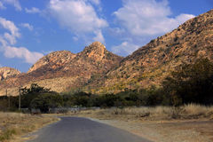 Tar Road Large Mountains. Picture of a Tarred Road with Large Pointed Mountains and Blue Sky Stock Image