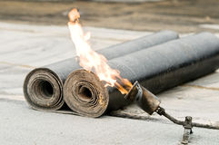 Tar roofing felt roll and blowpipe Stock Images