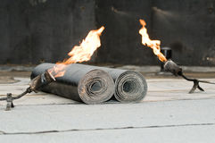 Tar roofing felt roll and blowpipe. Roofing felt roll and two torch blowpipes with open flame Stock Image