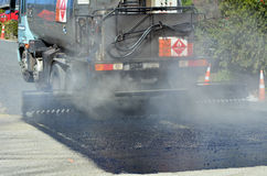 Tar truck vehicle tarring a piece of new road Royalty Free Stock Photography