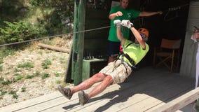 Tara, Montenegro - 30 de junio de 2017 El hombre mayor con grito va en viaje peligroso Línea zorro de la cremallera de las montañ metrajes