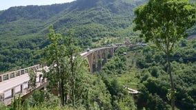 Tara, Montenegro - 30 June, 2017. Tara canyon bridge Durdevica above river Montenegro. Big truck drive by Tara Bridge. High Tara canyon. Transportation lorry stock video