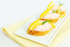 Taramasalata canape fish-roe spread bites with lemon slices over bread Royalty Free Stock Image
