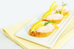 Taramasalata-Canapefischrogen verbreitete Bisse mit Zitronenscheiben über Brot Lizenzfreies Stockbild