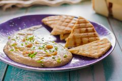 Taramasalata and pita grill on a ceramic violet plate side view royalty free stock photo