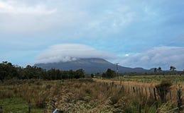 Taranaki in beanie of clouds Stock Photos