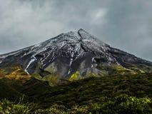 Taranaki of zet egmont vulcano met sneeuw in bewolkte avond op stock foto