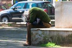 Taranto Apulia, Włochy,/- 03/23/2019: Przegrany bezdomny stary człowiek deprymujący na ławce zdjęcie stock