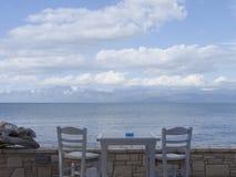 Tarasowy widok z szarym stołem i dwa szarymi krzesłami, morze, chmurnieje fotografia royalty free