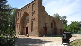 Taraz Karakhan Mausoleum. Picturesque side view of the main entrance with park trees on a sunny blue sky day stock footage