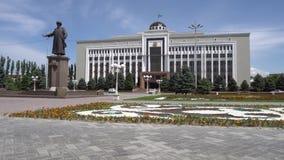 Taraz Regional Akimat. City hall with waving kazakh flag at background with statue of Jambyl Jabayev side view on a sunny blue sky day stock video footage