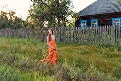 Tarde da noite na jovem mulher em uma vila retro attire caminhadas ao longo da paliçada velha e da casa rural fotos de stock