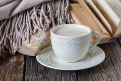 Tarde de la caída con el libro caliente de la tela escocesa y el té con leche caliente imagenes de archivo