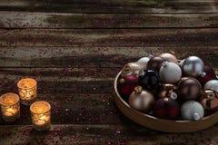 Tarde de la Navidad con las chucherías y las luces de una vela pacíficas en la madera rústica Fotos de archivo