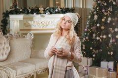 Tarde de la Navidad Mujer rubia hermosa joven con la taza de café en apartamentos clásicos una chimenea blanca, adornada fotografía de archivo