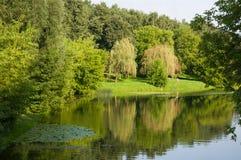 Tarde del verano en los bancos del río entre los árboles dos muchachas y bicicletas Imágenes de archivo libres de regalías