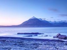Tarde en el lago Scavaig con las montañas de Cuillins en luz caliente de la puesta del sol Foto de archivo libre de regalías