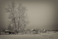 Tarde en el pueblo, Rusia, foto blanco y negro, antigüedad entonada del invierno foto de archivo