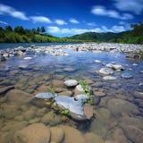 Río debajo del cielo azul Imagenes de archivo