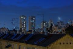 Tarde en la ciudad, cuartos residenciales iluminados Imagen de archivo