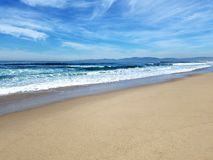 Tarde ensolarada na praia com nuvens claras Fotografia de Stock