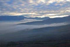 Tarde. niebla en las montañas Fotos de archivo libres de regalías
