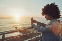 Tarde, puesta del sol, señora negra que toma la foto de ella Imagen de archivo libre de regalías