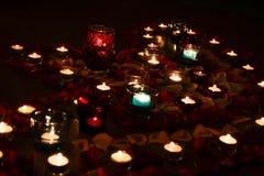 Tarde romántica por luz de una vela con los pétalos color de rosa Fotos de archivo libres de regalías