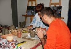 Tarde tradicional que se sienta con la gente que hace la cerámica imagen de archivo