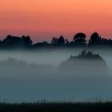 Tarde y puesta del sol brumosas Imagenes de archivo