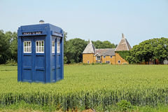 Tardis in crop field. Photo of time lord dr who tardis landing in kent crop field with oast house in background Royalty Free Stock Photos