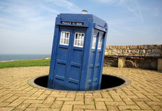 Tardis emerges from black hole. Photo of dr who tardis time machine emerging from a galactic worm hole and landing by the coast in whitstable in the county of Stock Photography