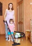 Tareas de la madre y de la hija con el aspirador Foto de archivo libre de regalías