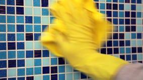 Tarefas da casa - limpando a parede do banheiro com o pano de limpeza e o spr vídeos de arquivo