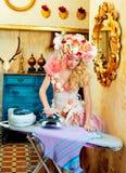 Tarefas louras do ferro da mulher da dona de casa da forma barroca Imagem de Stock Royalty Free