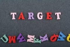 TAREGET-ord på svart brädebakgrund som komponeras från träbokstäver för färgrikt abc-alfabetkvarter, kopieringsutrymme för annons Arkivfoton