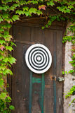 Dartboard on door. Dartboard target on wooden door surrounded by green leaves Royalty Free Stock Photo