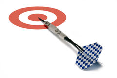 On Target. A single blue and white finned dart laying on a red and white bull's-eye target. Conceptual business image for being 'on target', 'moving forward' stock photos