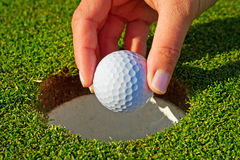 At the target. Hand taking golf ball from the hole Royalty Free Stock Images