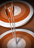 Target and arrow background, business goal. Two orange targets in a row, three arrows hits the first one in the center, vertical background Stock Images