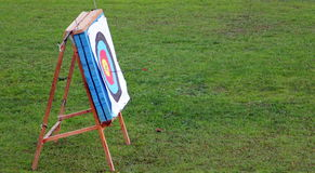Target with arrows in it. Archery target with some arrows in it in green field Royalty Free Stock Photos