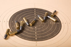 Target and bullets. Target and several .22 caliber bullets (focus on center stock image