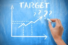 Target concept with business woman drawing growing arrows on chalkboard royalty free stock photo