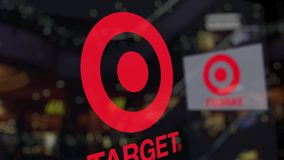 Target Corporation logo on the glass against blurred business center. Editorial 3D rendering. Target Corporation logo on the glass against blurred business stock video footage