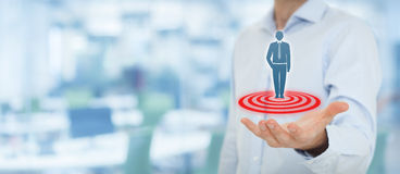 Target customer. (marketing) concept. Businessman hold  represented by virtual icon of man standing on target. Wide banner composition, office in background Stock Image